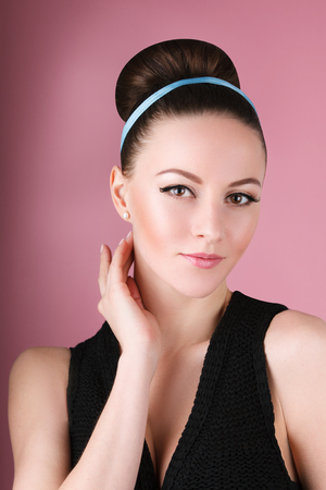 Portrait oflady with clean make-up and hair bun in the pink background in retro 60s style vintage