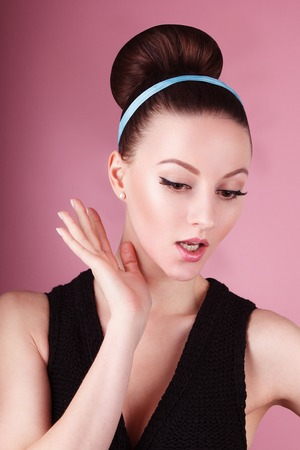60's: Portrait oflady with clean make-up and hair bun in the pink background in retro 60s style vintage