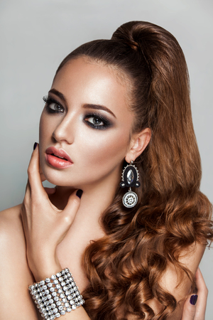 cola mujer: Belleza morena chica modelo de moda con pelo largo y castaño rizado sano y brillante joyas Foto de archivo