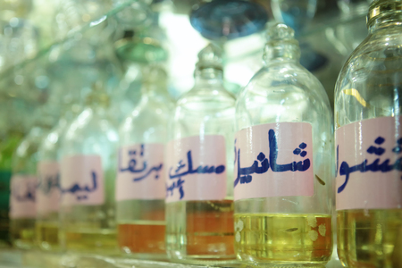 attar: Closeup of bottles of essential oils used in perfume making displayed in a row on the shelf Stock Photo