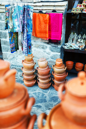 a jar stand: clayware souvenirs sold on a local market in the old town of Sheki, Azerbaijan on Karavan Saray street