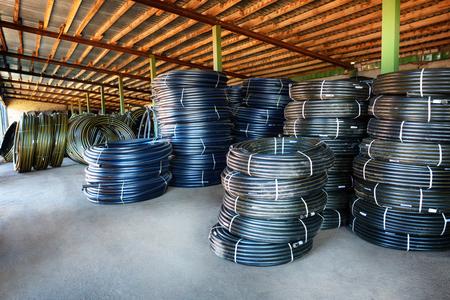 kunststoff rohr: Stapel von Rollen schwarz PVC-Kunststoff-Rohr im Freien mit selektiven Fokus außerhalb des Lagers
