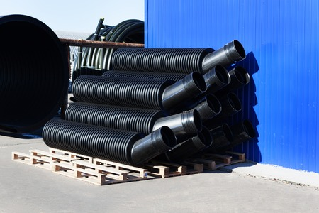 plastic conduit: stacks of black pvc plastic pipe outdoors with selective focus outside the warehouse Stock Photo