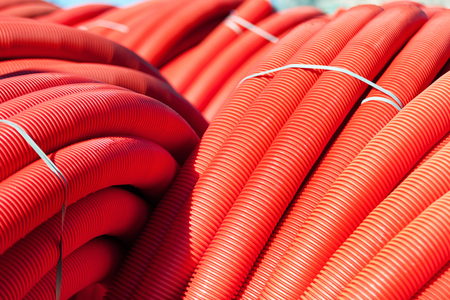 plastic conduit: Tubing. Red plumbing pipe plastic pvc close-up. Stock Photo