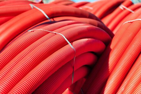 plastic conduit: Tubing. Red plumbing pipe plastic pvc close-up. Stock Photo