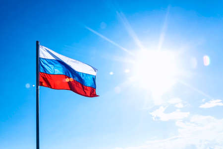 sun flare: Russian flag on blue sky background with sun flare and rays