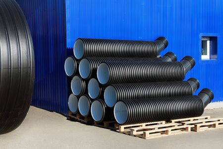plastic conduit: stacks of black pvc plastic pipe and treatment plant outdoors outside the warehouse