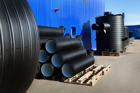 kunststoff rohr: stacks of black pvc plastic pipe and treatment plant outdoors outside the warehouse