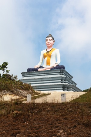 gambling stone: Statue of sitting Buddha in the clouds fog, Cambodia, Bokor Mountains, Kampot province