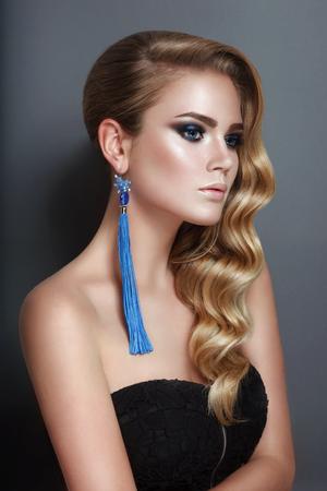 Beautiful blonde with curls, blue ear-rings jewelry. Beauty face in grey studio background