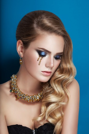 Beautiful blonde with curls, golden tear make-up and gold necklace jewelry. Beauty face in blue studio background Stock Photo