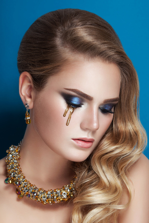 marilyn: Beautiful blonde in a Hollywood manner with curls, golden tear make-up and gold necklace jewelry. Beauty face in blue studio background