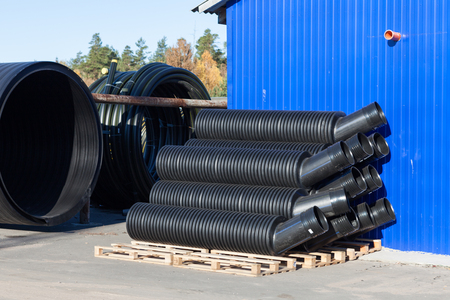kunststoff rohr: stacks of black pvc plastic pipe outdoors with selective focus outside the warehouse Lizenzfreie Bilder