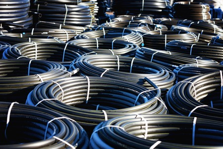 plastic conduit: stacks of rolls black pvc plastic pipe outdoors with selective focus outside the warehouse