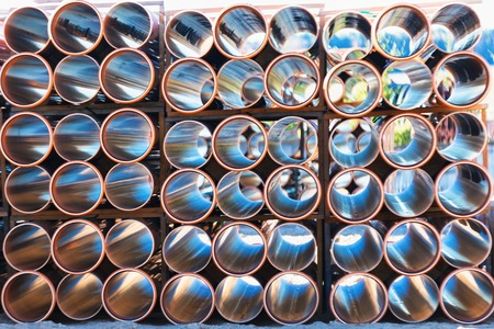 public housing: background of colorful big orange plastic pipes for hot water used at the building site close-up stack of pvc outside warehouse Stock Photo