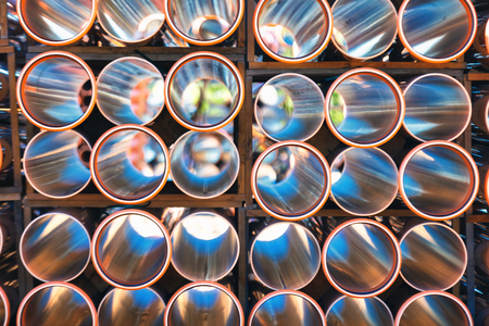 culvert: background of colorful big orange plastic pipes for hot water used at the building site close-up stack of pvc outside warehouse Stock Photo