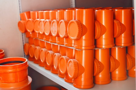 draining: PVC fitting in the white warehouse - a draining tee revision orange pipe Stock Photo