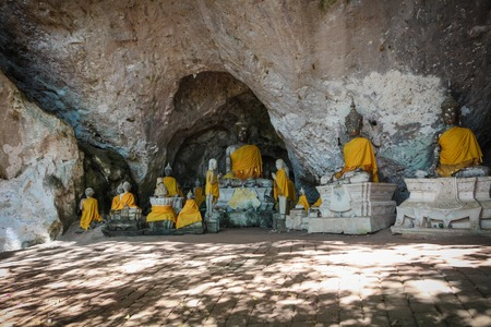 Tham Lab Laa or Tham Nang Thong near Chumphon, Thailand. Ancient cave with stalactites stalagmites temple in the mountain and many statues of buddha