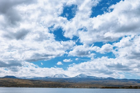 repulse: the view on mountains from the pier of Sevan lake and white clouds on blue sky on a sunny day, Armenia Stock Photo