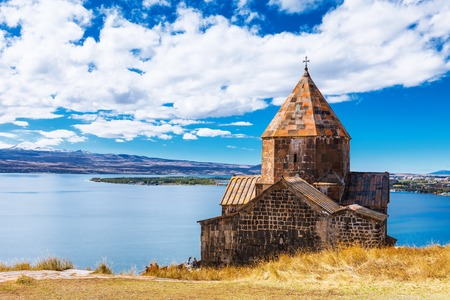Scenic view of an old Sevanavank church in Sevan, Armenia on sunny day blue sky and fluffy clouds