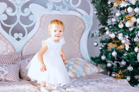 blinders: Little girl in white dress standing in the Christmas decorated room on the bed Stock Photo