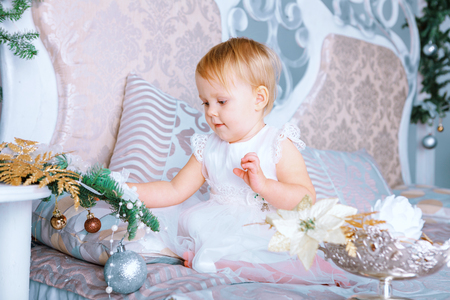 blinders: Little girl in white dress decorates tree in the Christmas decorated room on the bed Stock Photo