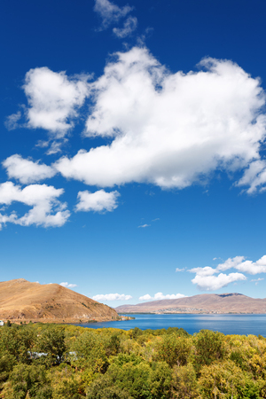 the view on mountains from the pier of Sevan lake and white clouds on blue sky on a sunny day, Armenia Stock Photo