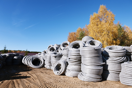 plastic conduit: Stack of coiled grey silver plastic pvc Polyethylene Corrugated drainage pipes for sewer system outdoor warehouse on sunny fall autumn day blue sky orange yellow birch trees.