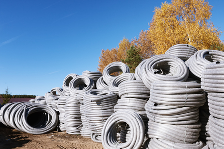 Stack of coiled grey silver plastic pvc Polyethylene Corrugated drainage pipes for sewer system outdoor warehouse on sunny fall autumn day blue sky orange yellow birch trees.