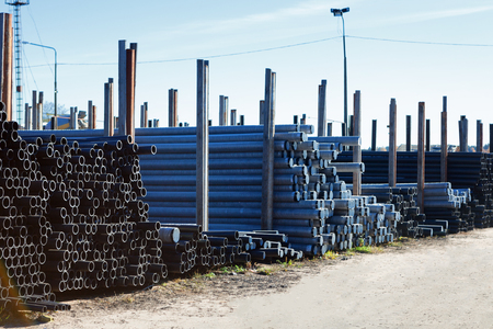 plastic conduit: stacks of black pvc plastic pipe outdoors outside the warehouse
