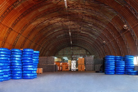 pvc Plastic pipes stacked in a warehouse yard use plumbing or sewage installations on construction site, packed for shipping, orange roof