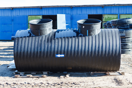 pvc black treatment plant outdoors outside the blue warehouse. Polyethylene well for drainage systems