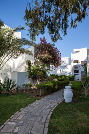 Hurgada, Egypt - 11 August 2014: white wall hotel entrance area with path, palms in the idyllic green garden, white vase
