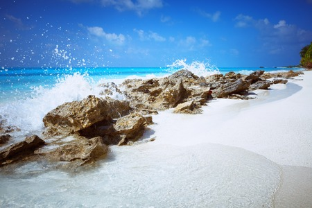 Scenic view of Wild idyllic Beach at Maldives island Fulhadhoo with white sandy beach and sea, stones, rocks and wave Stock Photo