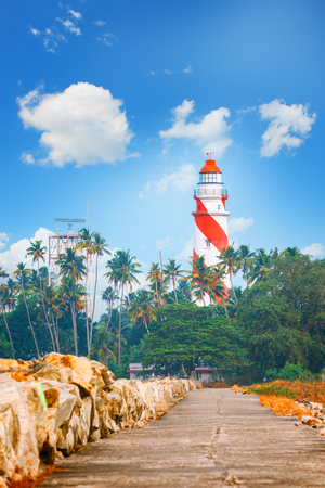 Thangassery red and white stripe Lighthouse on the cliff Quay breakwater surrounded by palm trees and big sea waves on the Kollam beach. Kerala, India Stok Fotoğraf