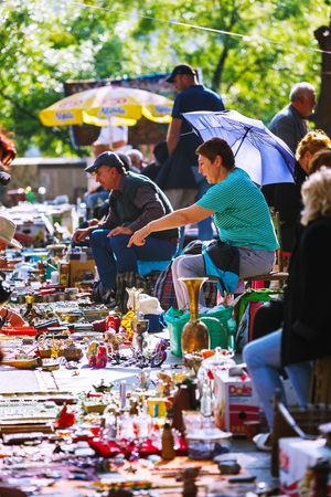 Tbilisi, Georgia - 08 October, 2016: An unidentified seller on Dry Bridge Flea market in Tbilisi sells Soviet badges and icons, retro junk stuff, tableware set, dishes