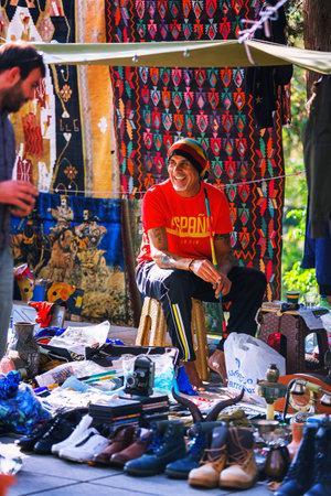 collectible: Tbilisi, Georgia - 08 October, 2016: An unidentified rastafari seller on Dry Bridge Flea market in Tbilisi sells Soviet badges and icons, retro junk stuff, tableware set, dishes Editorial