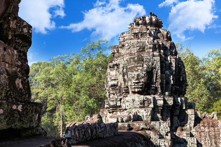 Massive stone faces carved into the sides of Wat Bayon temple in Angkor, Cambodia