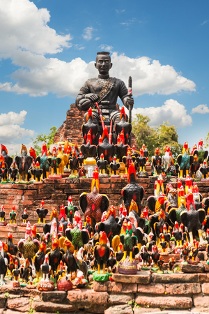 Statue of black Buddha head guarded by hundreds of roosters at Wat Thammikarat temple in Ayutthaya Province, Thailand Also called rooster temple