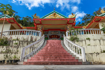 Main stair to Chinese Sangthom Temple of the Goddess of Mercy Shrine in Chaloklum, Ko Pha Ngan, Thailand Showing the ornate, orange roof of the main pagoda and the surrounding jungle.