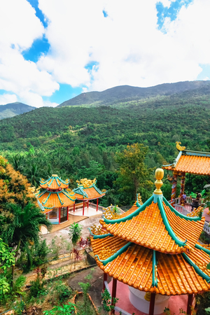 Beautiful view of Chinese Sangthom Temple of the Goddess of Mercy Shrine in Chaloklum, Ko Pha Ngan, Thailand Showing the ornate, orange roof of the main pagoda and the surrounding jungle.
