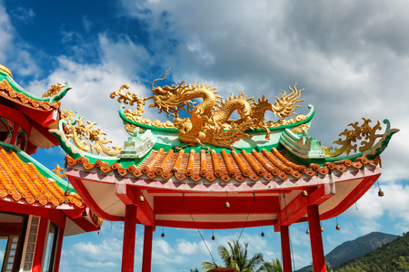 gazebo with a golden dragon on the roof of Chinese Sangthom Temple of the Goddess of Mercy Shrine in Chaloklum, Ko Pha Ngan, Thailand Showing the ornate, orange roof of the main pagoda and the surrounding jungle.