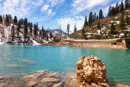 Frozen crystal blue lake and snowy woodland in winter Georgia. Shaori lake, Racha. Caucasus. Colorful vibrant outdoors on a sunny day 版權商用圖片