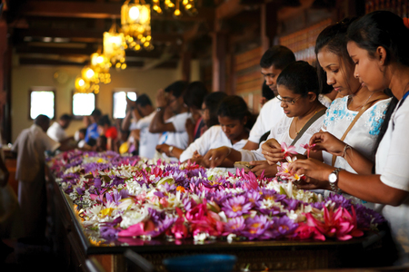 Kandy, Sri Lanka - 5 February 2017: Group of tourists and worshipers inside of the Temple of the Buddha Tooth. Sacred Tooth Relic of the Buddha attracts pilgrims and tourists to holy city of Kandy.