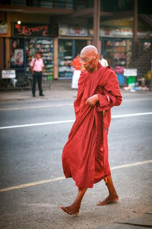 Ambalangoda, Sri Lanka - 02 February, 2017: Regular public Sri Lankan bus stop. Moring traffic in the city. People wait for the bus to work. Buddhist barefoot monk walks the street Editorial