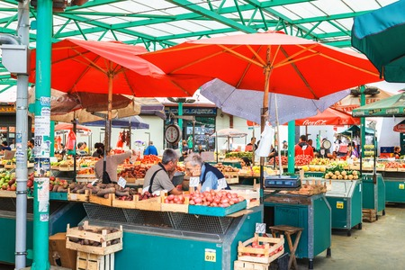 Belgrade, Serbia - 19 July, 2016: Different people at a farmers market buy and check grocery at Zeleni Venac in Belgrade, Serbia. Located on Trznica Pijaca Tvrdjava trade square