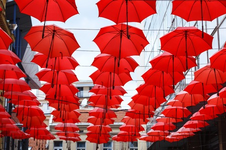 Decorative Red Parasol hang in a row Sunshade Ceiling towards the sky on central street of Belgrade
