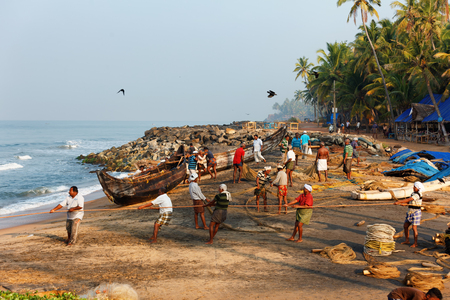 Varkala, India - February 09, 2016: Fishing net with many fishermen on backside the boat. Odayam beach, Varkala, India Redakční