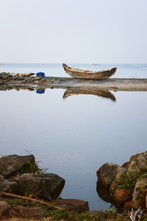 Lonely Wooden fishing boat anchored on the beach sand reflection in backwaters of Odayam beach near Varkala, Kerala, India Stock Photo