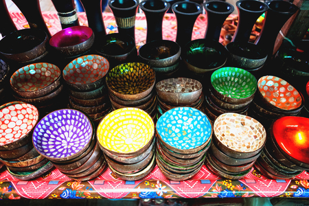 Colorful Coconut shell bowls on the wooden shelf. Souvenir coconut bowls selling on the market of Cambodia